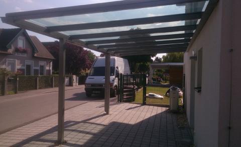 Kocsibeálló bécsben porfestett acél szerkezettel és ragasztott biztonsági üveg tetővel